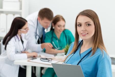 and medicine: Retrato de la sonrisa carpeta celebraci�n de la medicina doctora con documentos con sus tres colegas que trabajan en segundo plano. Salud y concepto de la medicina. Foto de archivo