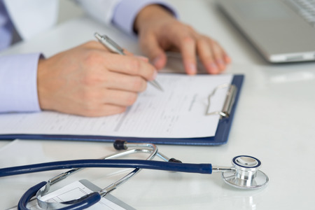 Stethoscope laying on medicine doctor's working table with doctor's hands writing on background. Healthcare and medical concept. Copyspace