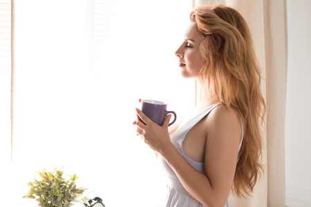 flavour: Young pretty woman standing with a cap of tea near the window. Calm sunny morning. Relaxation and happiness concept