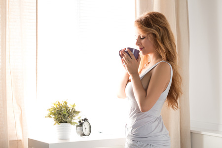 aroma: Young beautiful smiling woman standing near the window and holding a cap of tea. Calm sunny morning. Stock Photo