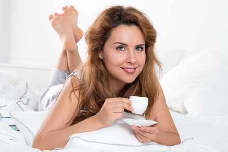 woman laying: Beautiful young woman laying on her bed and holding a cup of coffee in the morning