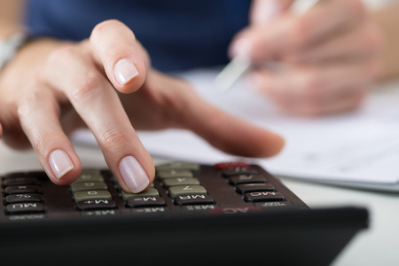 Accountant: Close up of female accountant or banker making calculations. Savings, finances and economy concept