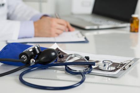 Medische manometer en stethoscoop die op geneeskunde arts werktafel. Doctor schrijftafeltje iets op de achtergrond. Medische hulp, preventie, preventie van ziekte of verzekering concept. Stockfoto - 46777712