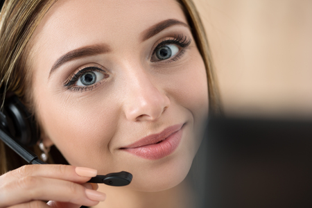 operator: Portrait of beautiful call center operator at work. Woman with headset talking to someone online Stock Photo