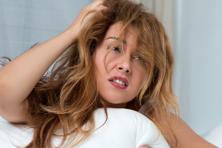 sleepiness: Young tousled woman waking up early in the morning