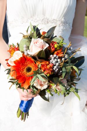 bouquets: Close up of bride hands holding beautiful autumn wedding bouquet.