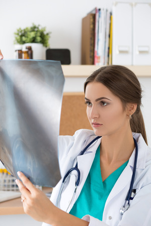 radiological: Young female doctor looking at lungs x-ray image. Healthcare and medical concept