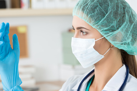 Female medicine doctor in protective mask and cap putting on blue protective glove. Healthcare and medical concept