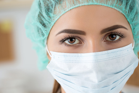 face mask: Close-up portrait of female medicine doctor wearing protective mask and cup. Healthcare and medical concept.