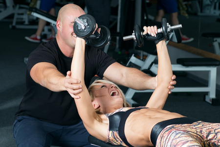 charming woman: Woman lifting dumbbells with her personal trainer in the gym. Weightlifting in sports club.