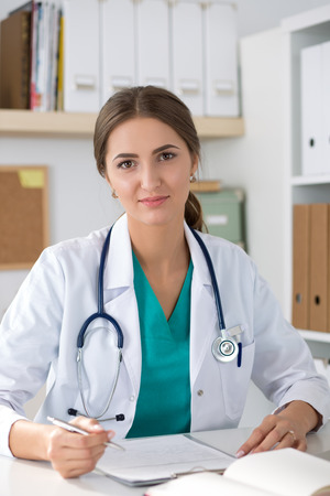 healthcare portrait: Portrait of smiling friendly medicine doctor sitting at her office. Healthcare and medical concept