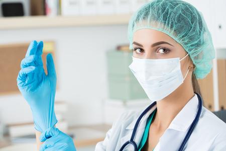 Vrouwelijke geneeskunde arts in beschermend masker en GLB zetten op blauwe beschermende handschoen. Gezondheidszorg en medische concept Stockfoto
