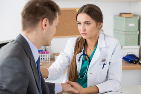 bad news: Friendly female medicine doctors holding male patients hand supporting him. Bad news, stress and depression concept.