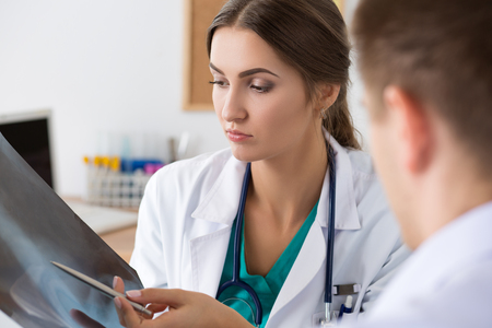 Female medicine doctor showing something to her male colleague on x-ray image. Healthcare and medical concept
