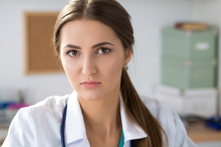 trust people: Close-up portrait of young serious medicine doctor sitting at her office. Healthcare and medical concept