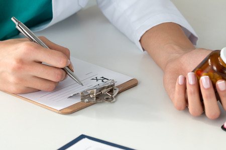 Close-up of doctors hands writing prescription and holding bottle with pills. Healthcare, medical and pharmacy concept.