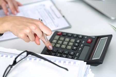 calculadora: Cierre de contable de sexo femenino o cálculos banquero decisiones. Ahorros, finanzas y economía de concepto