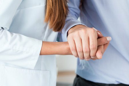healthcare office: Female medicine doctor helping her patient to walk after operation by supporting his hand. Hands close-up. Rehabilitation, kindness, healthcare and medicine concept