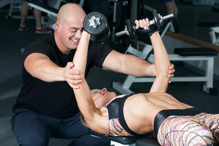 Mujer levantar pesas con su entrenador personal en el gimnasio. Levantamiento de pesas en el club deportivo.