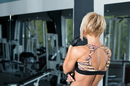 girl sport: Beautiful sportive girl standing back to camera and looking at gym preparing herself for the training Stock Photo