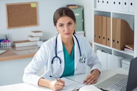 healthcare portrait: Portrait of young female medicine doctor sitting and working at her office. Healthcare and medical concept