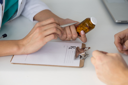 hand holding bottle: Close-up view of female doctors hand holding bottle with pills and writing prescription. Healthcare, medical and pharmacy concept.