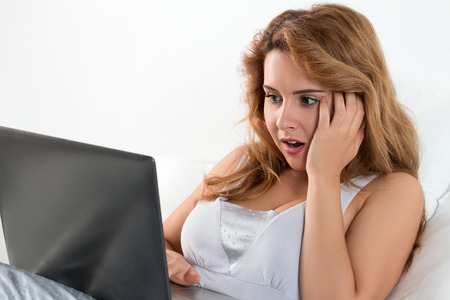 fear of failure: Young beautiful woman sitting at her bedroom and reading some shocking news at laptop