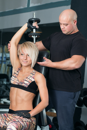 muscle woman: Woman lifting dumbbells with her personal trainer in the gym. Weightlifting in sports club.