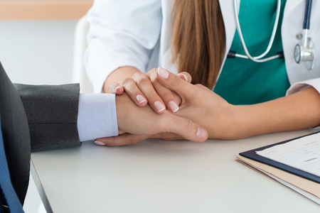 bad news: Close-up of friendly female medicine doctors hand holding male patients hand to support him. Bad news, stress and depression concept. Stock Photo
