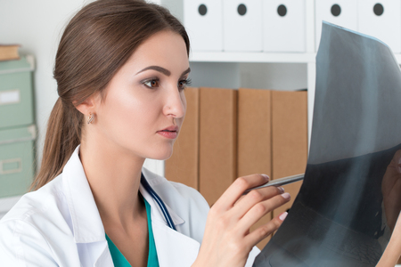 analyzing: Young female doctor looking at lungs x-ray image. Healthcare and medical concept