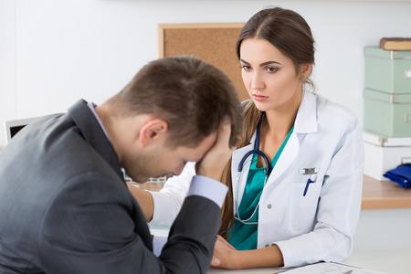 deprese: Přátelské ženský doktor medicíny drží mužské pacienta za ruku podporovat jej. Špatné zprávy, stres a deprese koncepce.