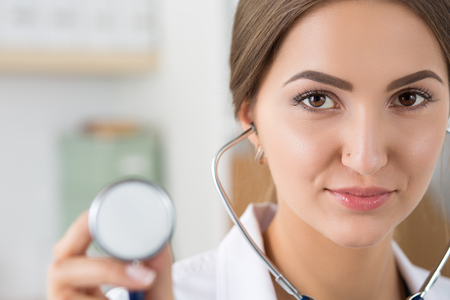 headshot: Portrait of beautiful female doctor holding stethoscope head ready to examine patient. Focus on eyes. Healthcare and medical concept
