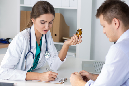 Female medicine doctor prescribing pills to her male patient. Healthcare, medical and pharmacy concept. Stock Photo