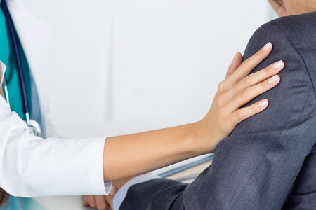 bad news: Close-up of friendly female medicine doctors hand touching male patients arm to support him. Bad news, stress and depression concept.