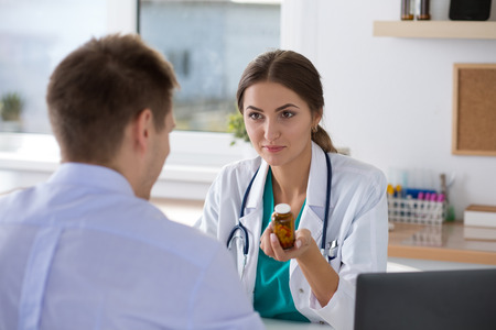 Female medicine doctor prescribing pills to her male patient. Healthcare, medical and pharmacy concept. Standard-Bild