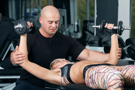 woman chest: Woman lifting dumbbells with her personal trainer in the gym. Weightlifting in sports club.