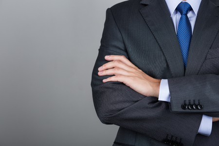 Business man with folded hands against gray background. Copy space Stockfoto