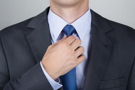 careerist: Well dressed business man adjusting his neck tie