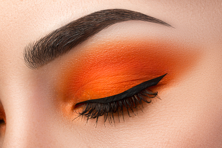 Close-up of woman eye with beautiful orange smokey eyes with black arrow makeup. Modern fashion make-up. Stock Photo