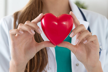 Close-up of female doctor hands holding read heart. Healthcare, cardiology and medical concept