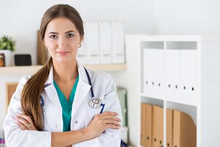 folded hands: Portrait of young friendly medicine doctor standing at her office with folded hands. Healthcare and medical concept Stock Photo