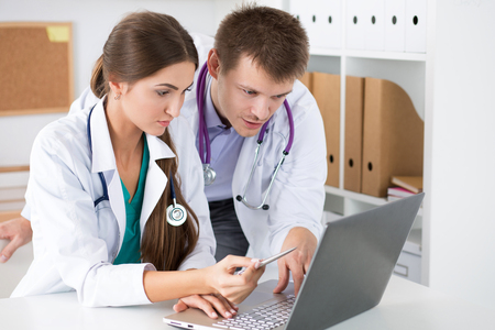 Two medicine doctors looking at laptop monitor standing at their office. Medical and healthcare concept