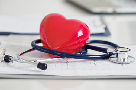 Stethescope and red heart lying on cardiogram. Healthcare, cardiology and mediacal concept