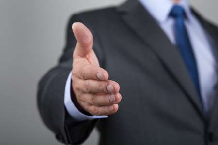 Businessman offering his hand for handshake. Greeting or congradulating gesture. Business meeting and success