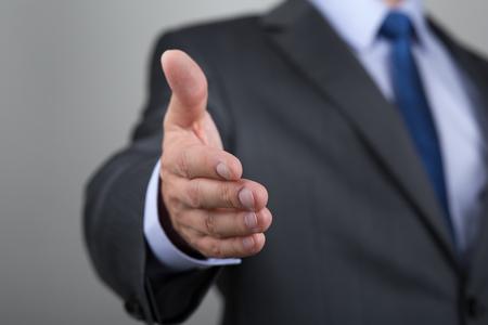 felicitaciones: El hombre de negocios que ofrece su mano para apretón de manos. Saludo o congradulating gesto. Reunión de negocios y el éxito