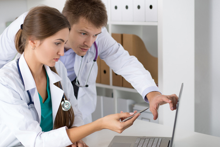 prescript: Two medicine doctors looking at laptop monitor standing at their office. Medical and healthcare concept