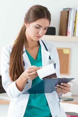 uniformes de oficina: medicina Mujer médico de pie en su oficina y mirando a la historia clínica del paciente. Cuidado de la salud y el concepto médico