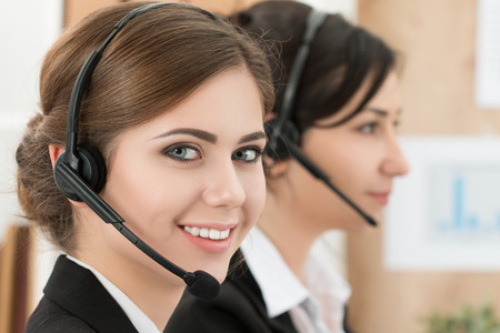 customer support: Portrait of call center worker accompanied by her team. Smiling customer support operator at work. Help and support concept