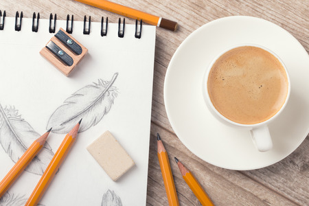 Close-up view of artists or designers table. Cup of coffee, pencils, sharpner and eraser laying on sketch book with hand-drawn feathers Stock Photo