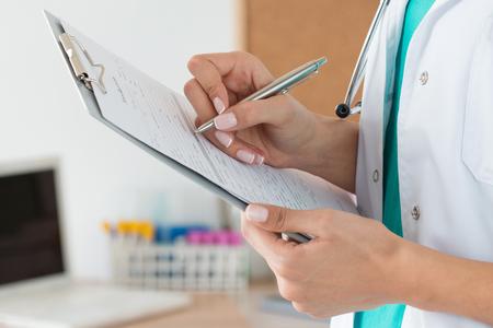 Close-up van vrouwelijke arts handen vullen patiënt inschrijvingsformulier. Gezondheidszorg en medische concept Stockfoto